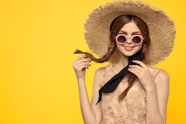 Romantyczna dama w słomkowym kapeluszu z okularami przeciwsłonecznymi