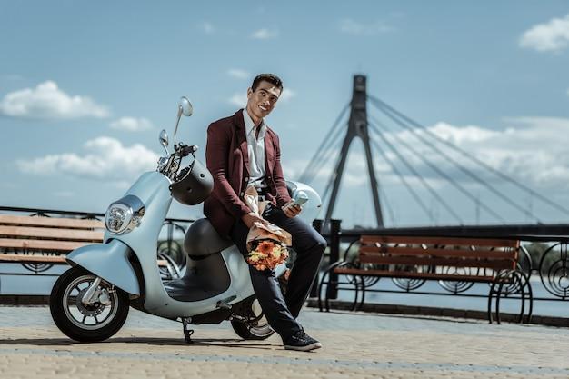 Romantyczna data. niski kąt przystojny zadowolony facet trzymający bukiet kwiatów i oparty na motocyklu