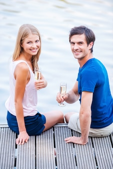Romantyczna data. piękna młoda kochająca para siedzi razem na nabrzeżu i trzyma kieliszki z winem