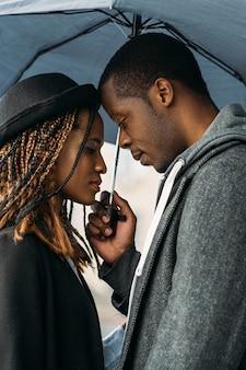 Romantyczna data. przetargu czarna para. afroamerykanin ładny związek, piękni młodzi ludzie w deszczowy dzień, stylowa koncepcja
