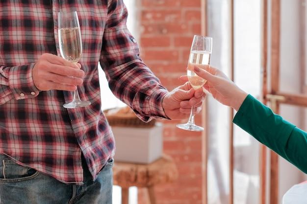 Romantyczna data. przycięte ujęcie faceta w kraciastej koszuli, który podaje kieliszek szampana swojej dziewczynie.