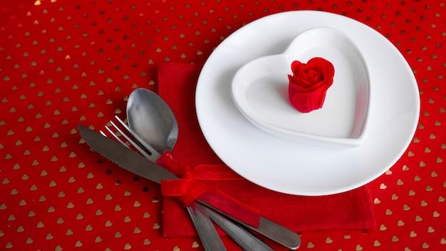 Romantyczna dekoracja świątecznego stołu. białe talerze w kształcie serca z czerwoną różą. czerwone tło