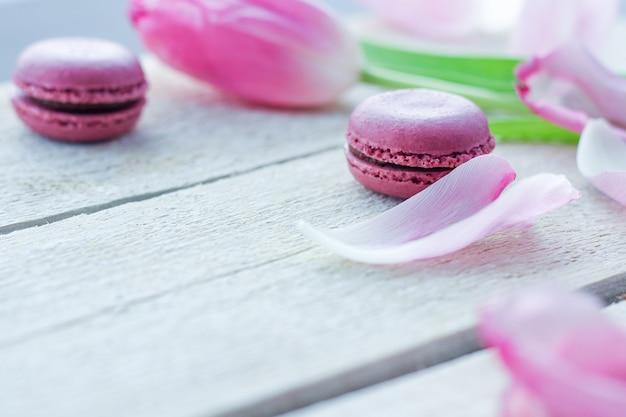 Romantyczna delikatna kompozycja z różowymi kwiatami i ciastkami makaronikowymi.