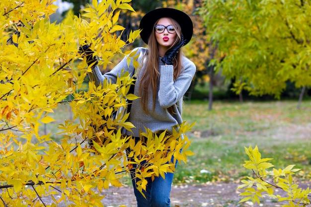 Romantyczna długowłosa dziewczyna pozuje z wyrazem twarzy pocałunek podczas spaceru w parku jesienią. zewnątrz portret eleganckiej europejskiej młodej kobiety w dżinsach i kapeluszu stojącym obok żółtego krzewu.
