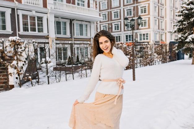 Romantyczna długowłosa kobieta w spódnicy pozuje na ulicy pełnej śniegu z latarnią. zewnątrz portret uśmiechnięta nieśmiała kobieta w białym swetrze zabawy w chłodne zimowe wieczory.
