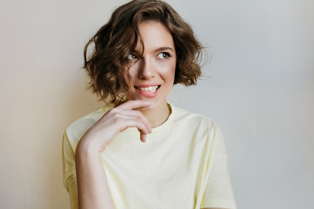 Romantyczna dziewczyna roześmiana figlarnie pozuje na jasnej ścianie. kryty portret marzycielskiej atrakcyjnej modelki z kręconymi włosami.