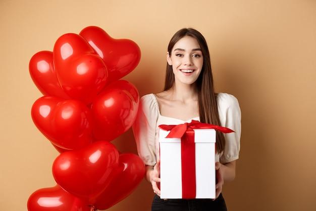 Romantyczna dziewczyna stojąca w pobliżu balonów w kształcie serca i trzymając prezent niespodziankę na walentynki