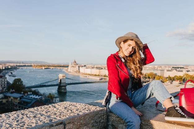 Romantyczna dziewczyna w czarnych gumowych butach siedzi na dachu i bawi się brązowymi włosami