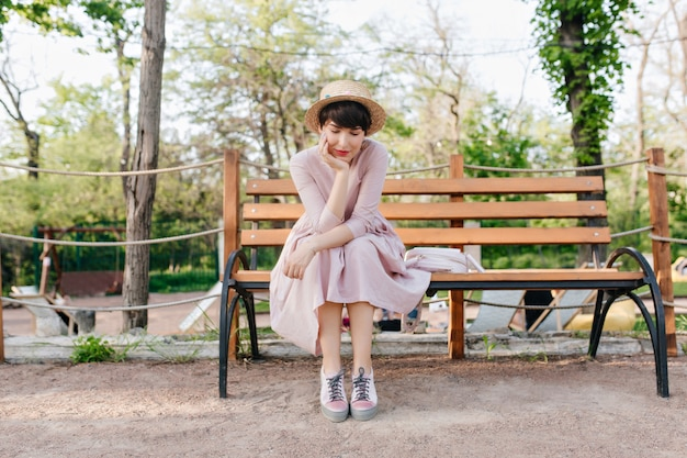 Romantyczna dziewczyna w modnym słomkowym kapeluszu siedzi na ławce w parku, podpierając twarz ręką i myśląc o czymś dobrym