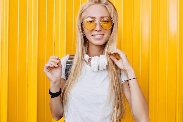 Romantyczna dziewczyna w żółtych okularach przeciwsłonecznych z zainteresowanym uśmiechem na jasnym tle. opalona dziewczyna z długimi blond włosami, śmiejąc się do kamery.