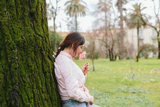 Romantyczna dziewczyna wącha kwiatu w ogródzie