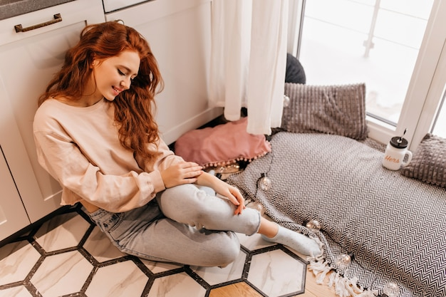 Romantyczna dziewczyna z długą fryzurą, siedząc na podłodze. imbirowa atrakcyjna pani spędzająca weekendowy dzień w domu.