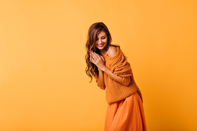 Romantyczna dziewczyna z falowaną fryzurą pozowanie na pomarańczowo z uśmiechem. wewnątrz portret niesamowitej białej kobiety w modnym swetrze.