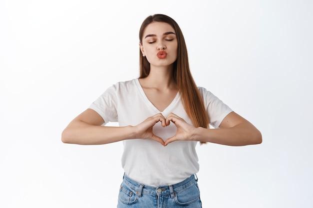Romantyczna dziewczyna zamyka oczy i całuje, pokazując pocałunek zmarszczone usta i znak serca, kocham cię gest, jak ktoś, biała ściana