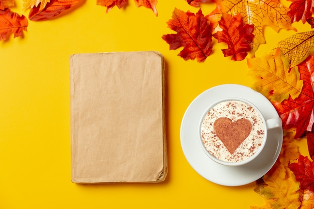 Romantyczna filiżanka kawy i książki z jesiennych liści na żółtym tle. widok z góry