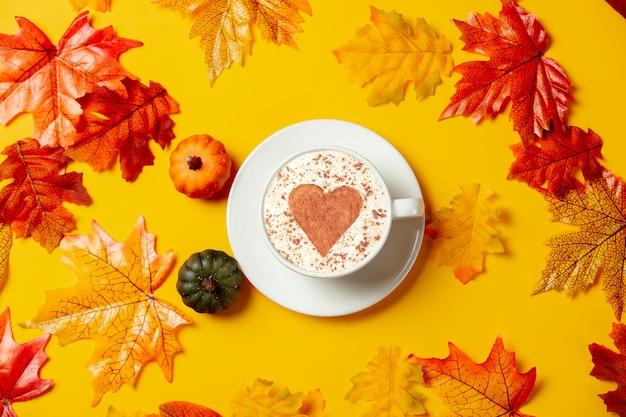 Romantyczna filiżanka kawy i małe dynie z jesiennymi liśćmi na żółtym tle. widok z góry