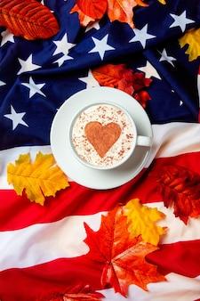 Romantyczna filiżanka kawy z jesiennych liści na tle flagi usa. widok z góry