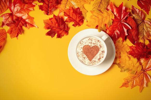 Romantyczna filiżanka kawy z jesiennych liści na żółtym tle. widok z góry