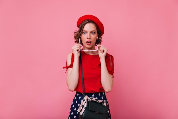 Romantyczna francuska dama pozuje z zaskoczonym wyrazem twarzy. kryty strzał z uroczą kręconą kobietą w czerwonym berecie na białym tle.