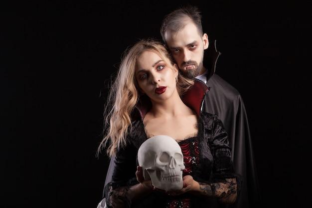 Romantyczna i nieśmiertelna para wampirów patrząca w kamerę na karnawał na halloween.