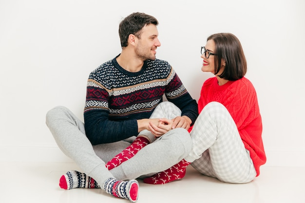 Romantyczna kobieta i mężczyzna trzymają się za ręce, patrzą na siebie z miłością