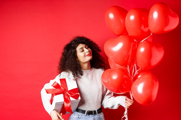 Romantyczna kobieta marzycielsko patrząc na balony serca od kochanka, trzymając prezent na walentynki w uroczym zapakowanym pudełku, stojąc na czerwonym tle.