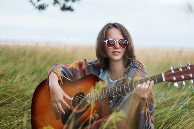 Romantyczna kobieta o krótkich, prostych, ciemnych włosach, ubrana w pelerynę i okulary przeciwsłoneczne podczas odpoczynku na zielonym polu, ciesząc się pięknym krajobrazem i grając na gitarze.