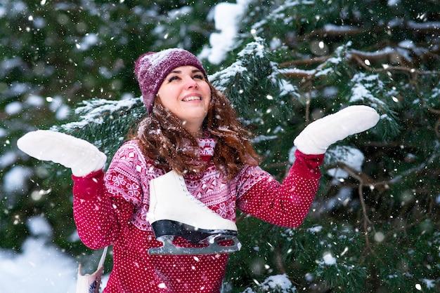 Romantyczna kobieta trzyma łyżwy zimowe na jej ramieniu. zimowe zabawy i sporty. dziewczyna łapie płatki śniegu w zimowym lesie