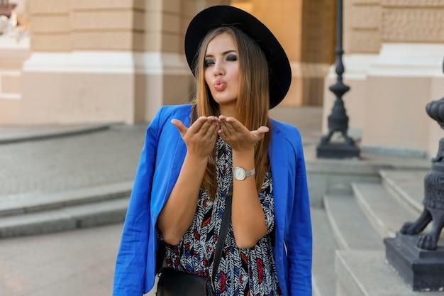 Romantyczna kobieta, ubrana w czarny kapelusz, niebieską kurtkę i elegancką sukienkę, przesyła buziaka do aparatu. pozowanie w starym europejskim mieście.
