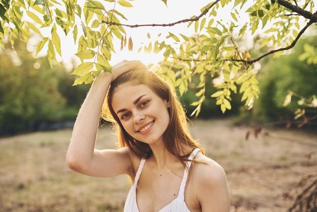 Romantyczna kobieta w białej sukni w pobliżu zielonych liści drzew na naturze w parku