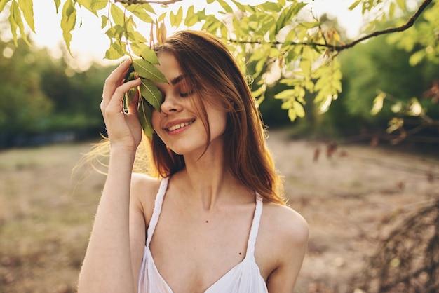 Romantyczna kobieta w białej sukni w pobliżu zielonych liści drzew w przyrodzie