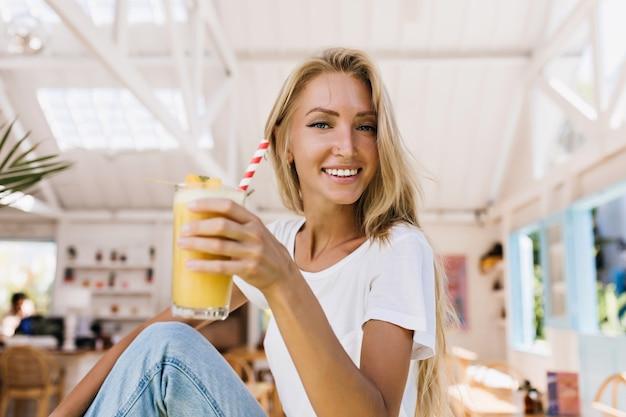 Romantyczna kobieta w dżinsach pije pomarańczowy koktajl z przyjemnością. kryty strzał uśmiechnięta blondynka trzyma szklankę zimnego soku siedząc w stołówce.