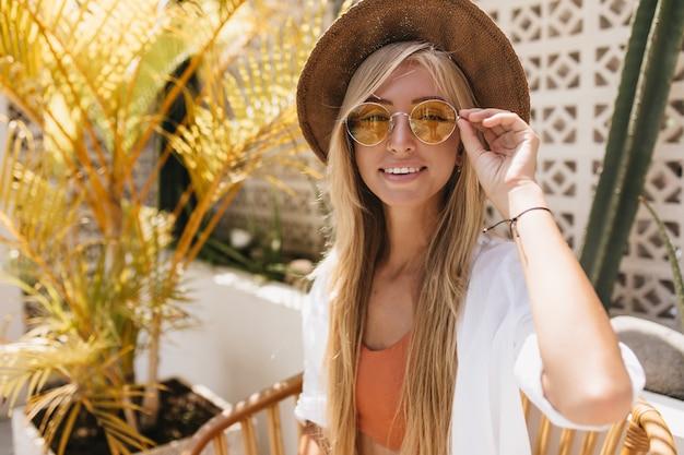 Romantyczna kobieta w kapeluszu z zainteresowanym wyrazem twarzy w kawiarni ośrodka. zewnątrz portret błogiej białej damy w okularach przeciwsłonecznych chłodzenie w weekend.
