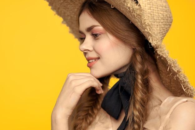Romantyczna kobieta w kapeluszu, zabawy na żółto i okulary przeciwsłoneczne