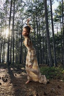 Romantyczna kobieta w lesie świeże powietrze sukienka drzewa tańczą.