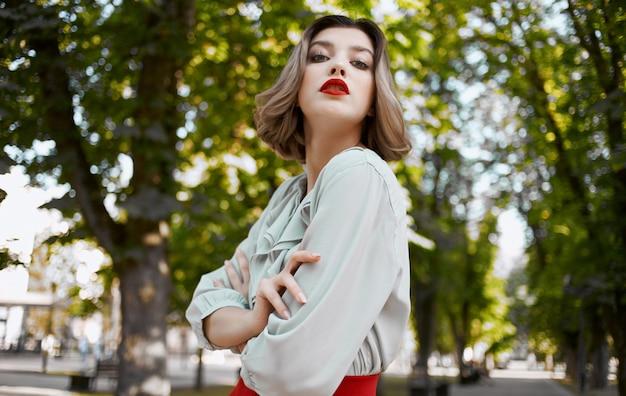 Romantyczna kobieta w spódnicy koszuli spaceru w parku latem w pobliżu zielonych drzew.