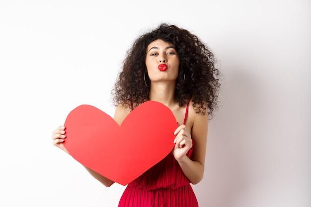 Romantyczna kobieta w sukience pokazującej duże czerwone serce, zmarszczone usta do pocałunku i wyrażenia miłości, wyrazić współczucie, białe tło.