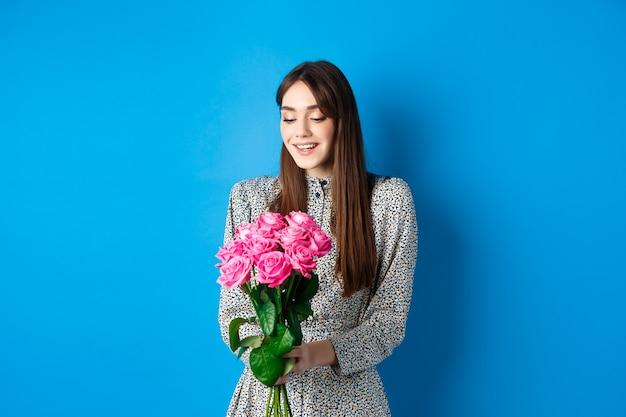 Romantyczna kobieta w sukience szczęśliwa patrząca na kwiaty