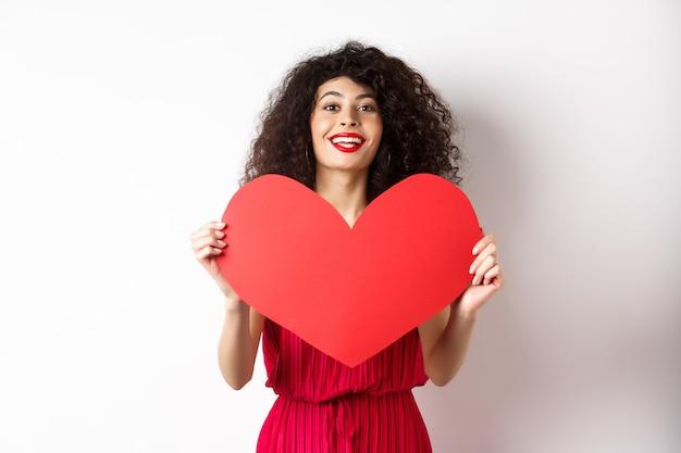 Romantyczna kobieta w sukni pokazującej duże czerwone serce, zakochana, uśmiechnięta szczęśliwa do kamery, białe tło.