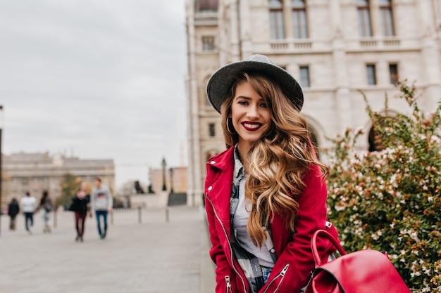 Romantyczna kobieta z długimi kręconymi fryzurami pozuje z uśmiechem podczas podróży po europie