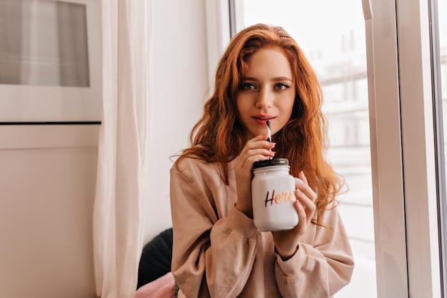 Romantyczna kobieta z falowanymi włosami pije cappuccino w domu. wewnątrz zdjęcie ślicznej europejskiej damy odpoczywającej w swoim pokoju.