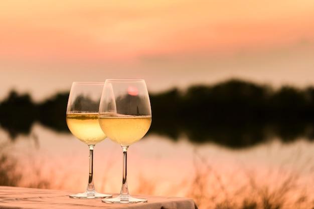 Romantyczna kolacja latem na plaży o zachodzie słońca z dwiema szklankami białego wina