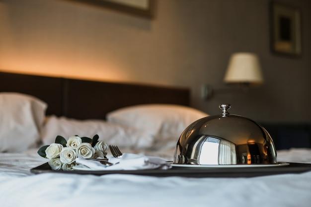 Romantyczna kolacja na łóżku z wiaderkiem z kwiatami