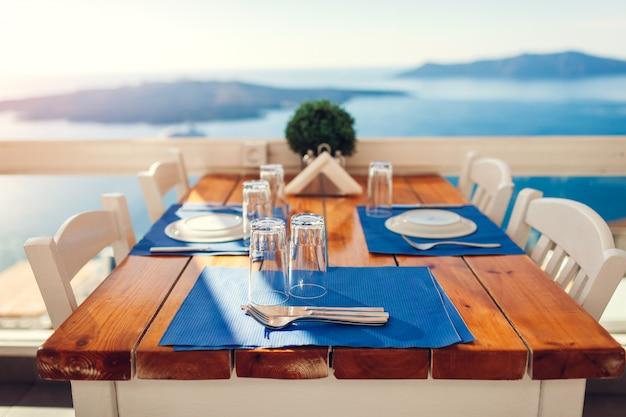 Romantyczna kolacja poślubna serwowana na wyspie santorini, grecja z nadmorskim i górskim krajobrazem, widok na wulkan.