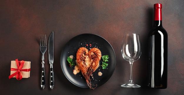 Romantyczna kolacja z krewetkami w kształcie serca i winem na brązowym tle. widok z góry z miejsca na kopię.