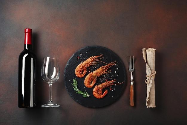 Romantyczna kolacja z krewetkami w kształcie serca i winem na brązowym tle. widok z góry z miejsca na kopię