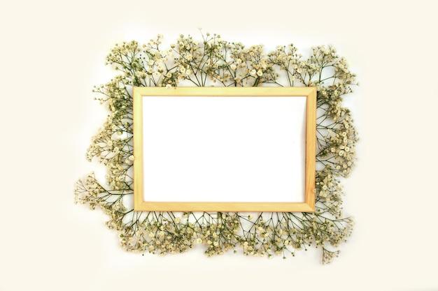 Romantyczna kompozycja kwiatów. białe kwiaty gipsówki, ramka na zdjęcia na białym tle.