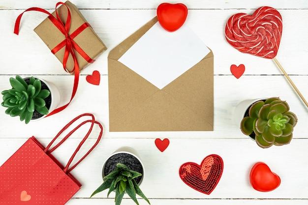 Romantyczna kompozycja z czerwonymi serduszkami, satynową tasiemką, lizakiem, pudełkiem prezentowym i papierową torbą na białej powierzchni