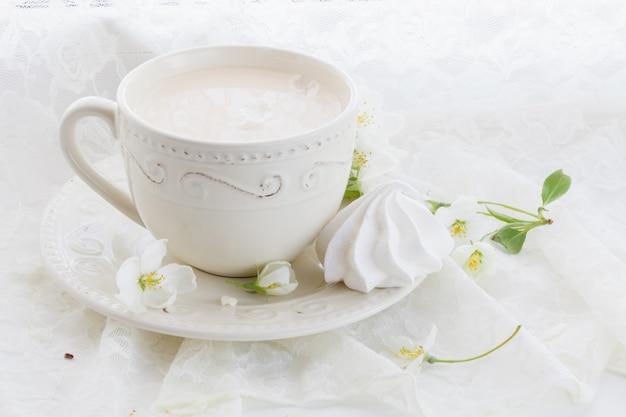 Romantyczna kompozycja z filiżanką herbaty, kwiatem zefiru i jabłkiem