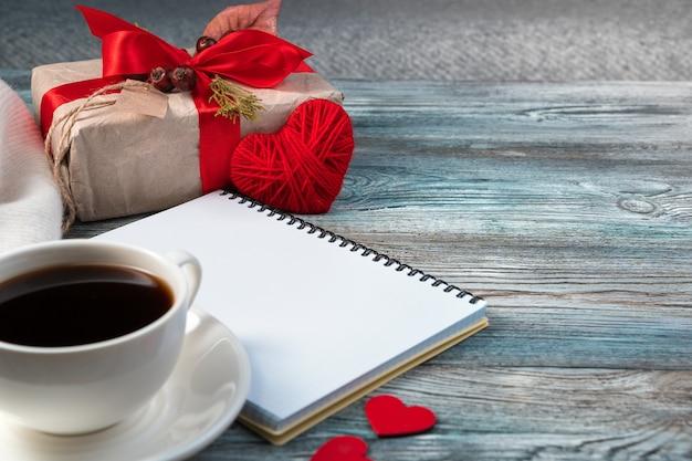 Romantyczna kompozycja z sercem, filiżanką kawy i prezentem.